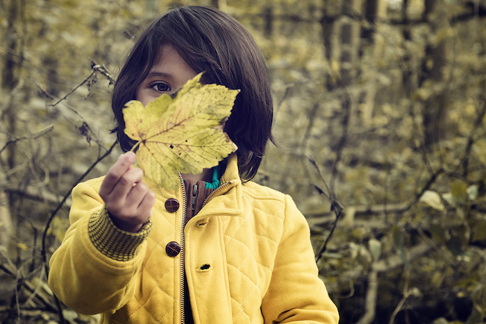 """Walk in the forest, autumn"" by Philippe Put: Child hiding face behind a leaf."