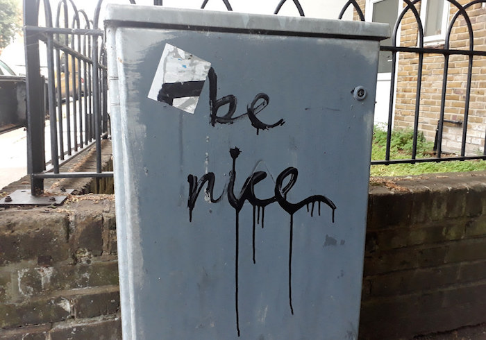 """Be Nice"" scribbled on a utility box."