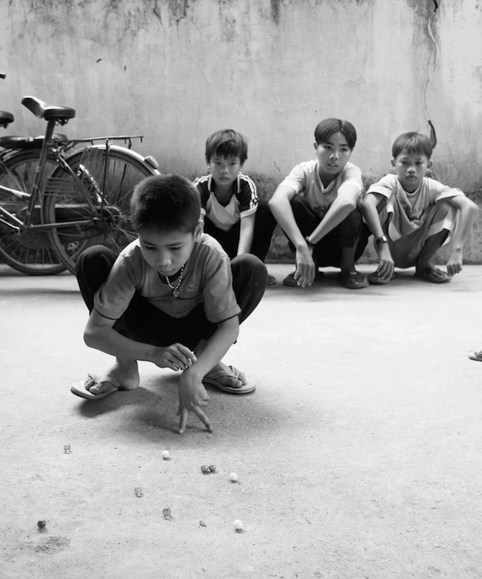 Children crouched playing marbles