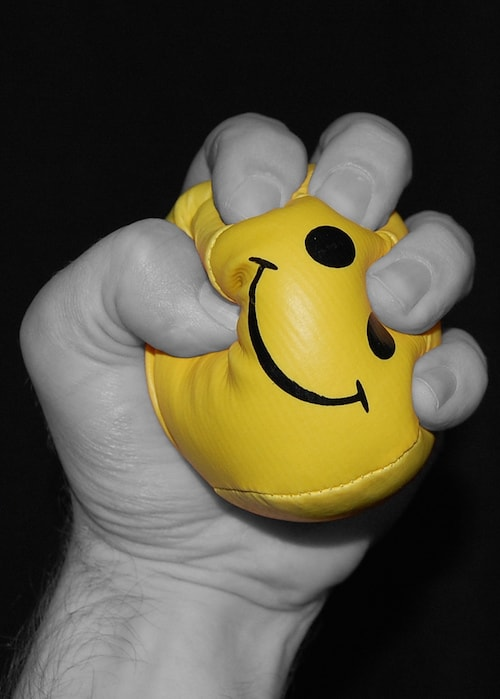 Fist squeezing smiley face ball