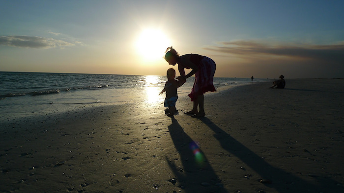 Mother and son on the beach at sunrise.