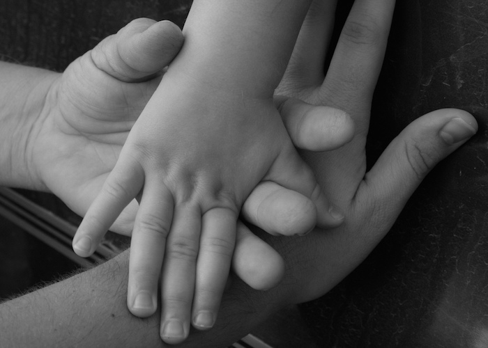 Three generations of hands stacked on one another