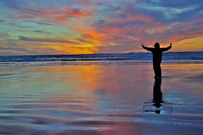 Person practicing qigong at sunset on a beach.