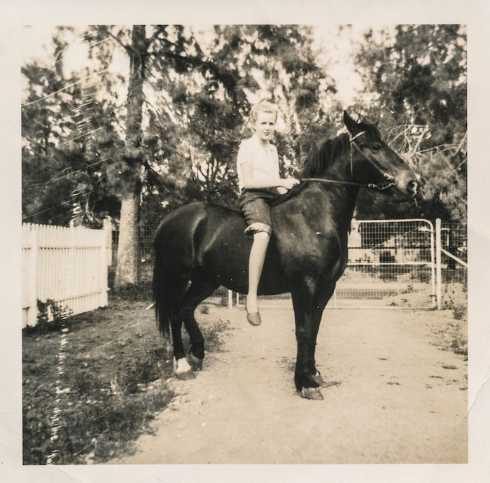 Young woman sits on the back of a black horse – May, 1947