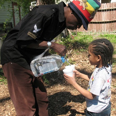 Man pouring water for little girl